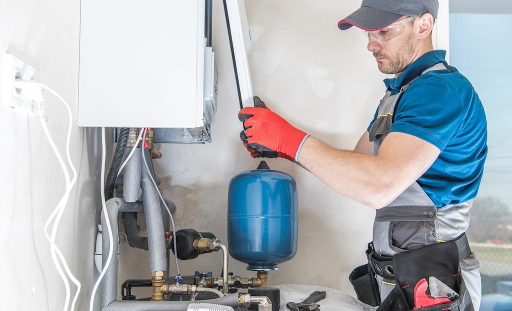 Installateur bezig met het onderhouden van een ketel