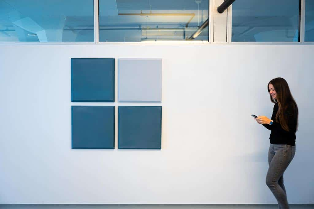 Bluace employee in front of Bluace's logo at the office