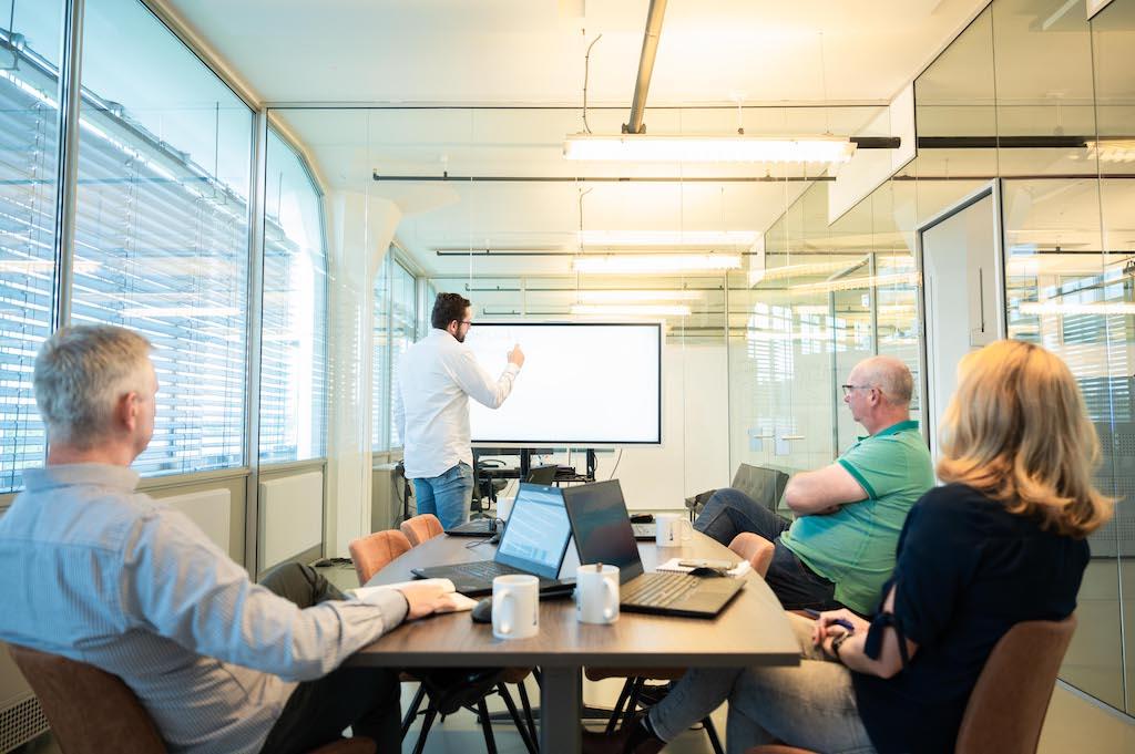 Projectteam is aan het vergaderen met mobiele apparaten en computers